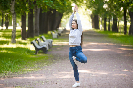 vriksasana: Serene beautiful sporty young woman working out in park alley, doing stretching exercise, standing in asana Vrikshasana (Vriksasana, Tree Pose), hands above head, full length