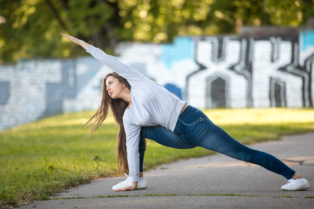 utthita: Beautiful sporty young woman working out on city street, doing warming up lunge exercise, Utthita Parsvakonasana, Extended Side Angle Pose, full length