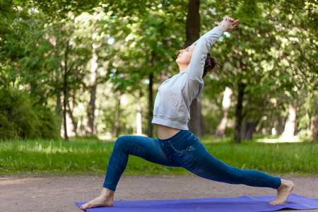 namaskar: Serene beautiful sporty young woman working out on blue mat on the street in park alley, doing high lunge exercise, virabhadrasana 1, warrior 1 posture, surya namaskar complex, full length Stock Photo