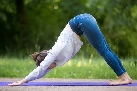 downward: Profile of beautiful sporty young woman working out on street, doing stretching exercises on blue mat in park alley, standing in downward facing dog pose, surya namaskar, full length Stock Photo