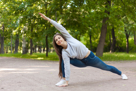 utthita: Smiling beautiful sporty young woman working out on road, doing warming up lunge exercise, Utthita Parsvakonasana, Extended Side Angle Pose, full length