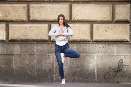 namaste: Sporty young woman on street working out in front of building wall, doing exercise for spine, standing in asana Vrikshasana (Vriksasana, Tree Pose), hands in Namaste, full length