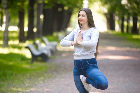 vriksasana: Portrait of calm beautiful sporty young woman working out in park alley, doing stretching exercise, standing in asana Vrikshasana (Vriksasana, Tree Pose), hands in Namaste Stock Photo