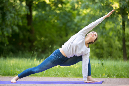 utthita: Profile of serene beautiful sporty young woman working out in park alley, doing warming up stretching exercise, standing in Utthita Parsvakonasana, Extended Side Angle Pose, full length