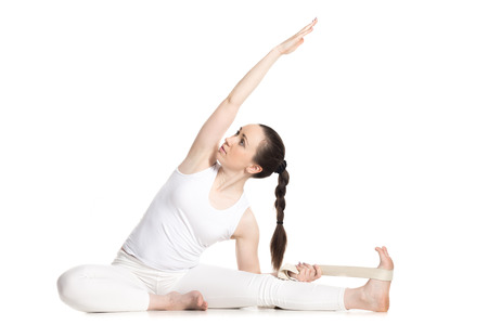 knee bend: Sporty beautiful young beginning yoga student in white sportswear sitting in Revolved Head to Knee pose, doing parivritta Janu Sirsasana simple variation with strap, studio full length isolated shot Stock Photo