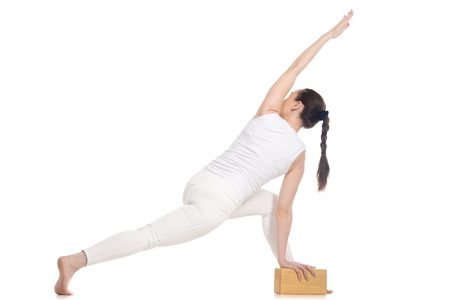parsvakonasana: Sporty beautiful young beginning yoga female student in white sportswear standing in easy variation of parivritta parsvakonasana with wooden yoga props, full length isolated studio shot, back view Stock Photo