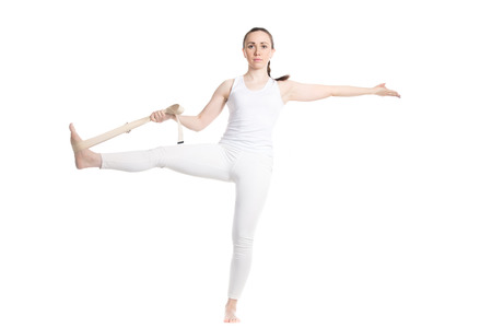 hasta: Sporty beautiful young beginning yoga female student in white sportswear standing in Utthita Hasta Padangushthasana, helping herself with strap, studio full length front view, isolated