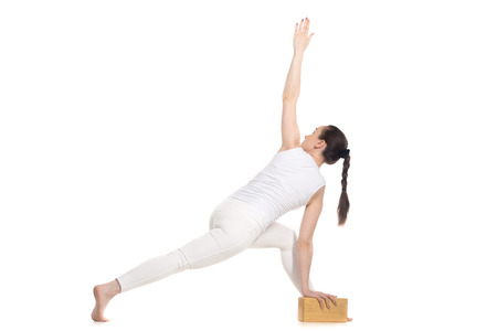 revolved: Sporty beautiful young beginning yoga female student in white sportswear standing in easy variation of parivrtta parshvakonasana with wooden block, full length isolated studio shot, back view