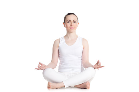 dhyana: Sporty beautiful young woman practicing yoga, Sitting in Easy (Decent, Pleasant Pose), Sukhasana, asana for meditation, pranayama, breathing, studio full length isolated shot, front view