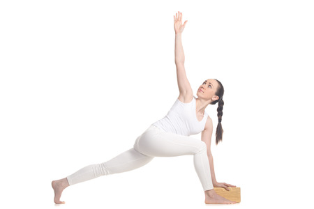 side angle pose: Sporty beautiful young woman in white sportswear doing lunge exercise for spine, standing in easy variation of Revolved Side Angle Pose with wooden block, full length isolated studio shot Stock Photo