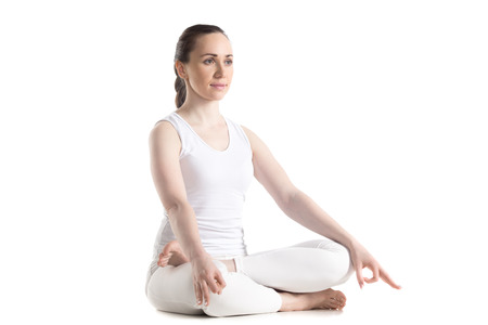 lotus: Sporty attractive young woman in white sportswear sitting in Ardha Padmasana, half lotus posture, studio full length three-quarters view, isolated