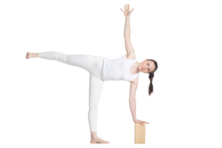 chandrasana: Sporty beautiful young cheerful female beginning yoga student in white sportswear standing in ardha chandrasana (Half Moon Pose) leaning on wooden block, studio full length isolated shot