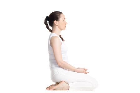 Deportivo mujer que practica yoga, sentado en el bloque de madera en seiza, vajrasana, rayo o asana de diamantes para la meditación, ejercicios de respiración, aislado estudio de longitud completa tiro, vista lateral, fondo blanco joven y bella Foto de archivo - 42895793