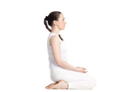 sporty beautiful young woman practicing yoga, sitting on wooden block in seiza, vajrasana, thunderbolt or diamond asana for meditation, breath work, studio full length isolated shot, side view, white background Stockfoto