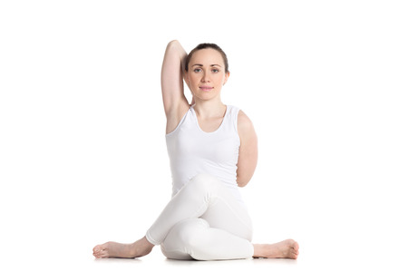 beautiful ankles: Sporty smiling beautiful young woman in white sportswear sitting in Gomukasana, Cow face pose, asana for hips, ankles, shoulders and chest, studio full length shot, front view, isolated
