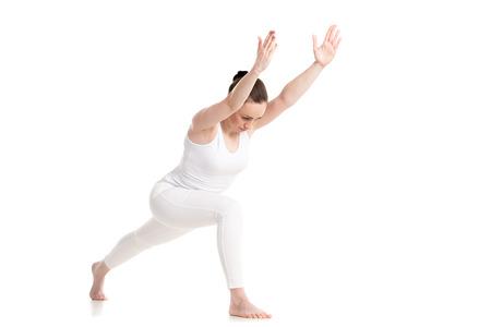 part of me: Mujer deportiva hermosa joven en ropa deportiva blanca haciendo ejercicio estocada, de pie en Warrior I postura variaci�n, tiro del estudio, aislado, longitud de tres cuartos ver, parte del gran serie de fotos
