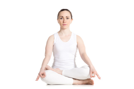 Sporty attractive young woman in white sportswear sitting in Ardha Padmasana, half lotus posture, studio full length front view, isolated