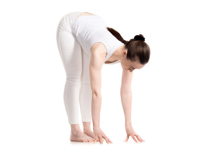 namaskar: Sporty beautiful young woman in white sportswear doing Intense Forward-Bending Pose, Uttanasana, full length shot, isolated studio three-quarters view, part of Surya Namaskar series