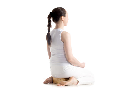 Sporty beautiful young woman practicing yoga, sitting on wooden block in seiza, vajrasana, thunderbolt or diamond asana for meditation, breath work, studio full length isolated shot, back view