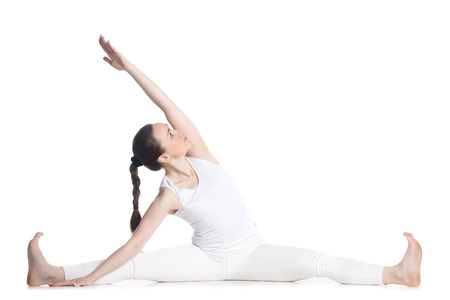 revolved: Sporty beautiful young woman in white sportswear sitting in easy variation of Parivrtta Upavistha Konasana, Revolved Seated Angle Pose, studio full length isolated shot, front view