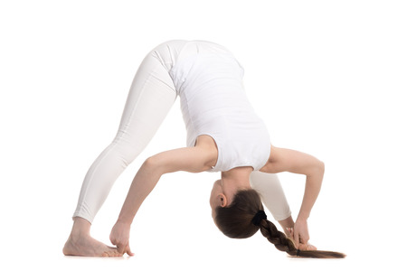 straddle: Sporty beautiful young woman in white sportswear doing Standing Straddle Forward Bend, Prasarita Padottanasana posture, studio full length three-quarters view on white background, isolated Stock Photo