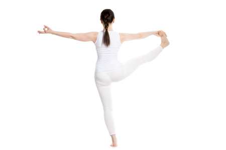 utthita: Sporty beautiful young woman in white sportswear standing in Utthita Hasta Padangushthasana, Extended Hand-To-Big-Toe yoga pose, studio full length back view, isolated Stock Photo