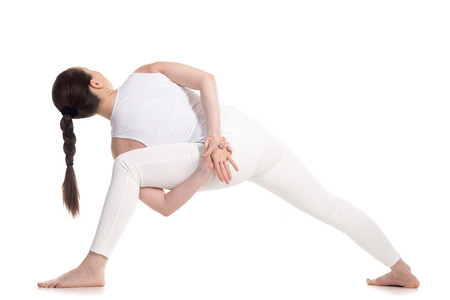 utthita: Sporty attractive young woman in white sportswear doing lunge exercise, variation of utthita parshvakonasana with hands behind back, part of large photo series, isolated, full length, rear view