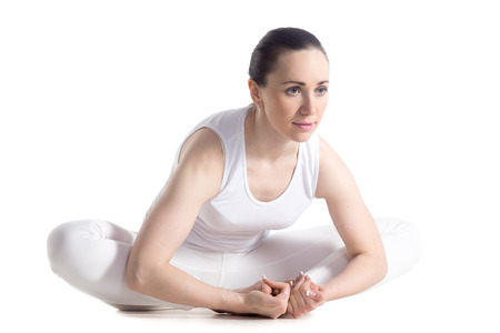 baddha: Sporty beautiful smiling young woman in white sportswear sitting in purna titli, bound angle, cobbler, butterfly pose, studio full length isolated shot, three-quarters view