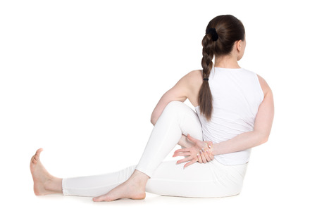 ardha: Sporty beautiful young woman in white sportswear practicing yoga, sitting in Twisted pose, variation of Ardha Matsyendrasana, studio full length isolated shot, back view