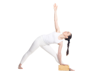 utthita: Sporty beautiful young beginning yoga female student standing in Utthita Trikonasana, Extended Triangle Pose with wooden block, studio full length profile view on white background, isolated