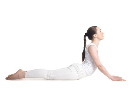 Sporty beautiful young woman in white sportswear doing cobra asana, bhudjangasana (Seal - yin yoga variation), studio full length side view, isolated