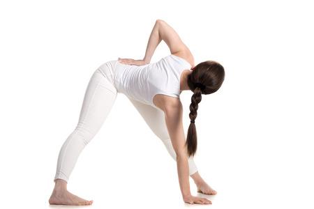 trikonasana: Sporty beautiful young woman in white sportswear standing in variation of Trikonasana yoga pose, studio full length three-quarters shot on white background, isolated, back view