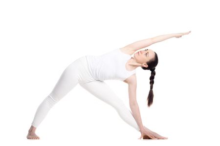 utthita: Sporty beautiful smiling young woman standing in Utthita Trikonasana, Extended Triangle Pose, studio full length profile view on white background, part of large photo series, isolated