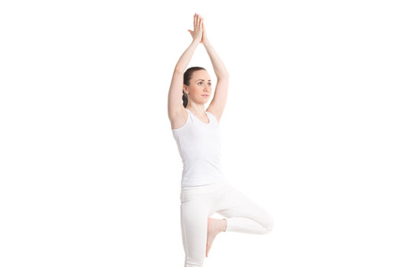 anjali: Portrait of sporty attractive young woman in white sportswear doing exercise for spine, vrksasana pose, hands above the head in Anjali mudra, part of photo series, isolated, full length