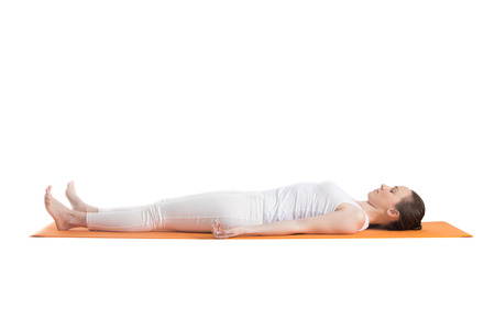 Sporty beautiful young woman in white sportswear lying with closed eyes on orange mat in Shavasana (Savasana, Corpse Pose), studio shot, isolated, full length side view