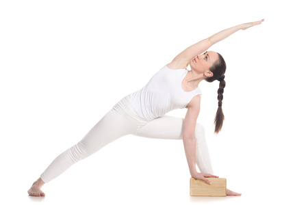 parsvakonasana: Sporty attractive young beginning yoga woman student in white sportswear doing lunge exercise for spine, utthita parsvakonasana with wooden brick, studio shot, isolated, full length