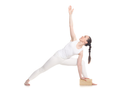 Sporty attractive young woman in white sportswear doing lunge exercise for back, utthita parsva konasana with wooden block, extended side angle pose, studio shot, isolated, part of large photo series