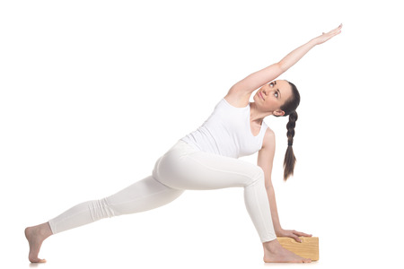 revolved: Sporty beautiful young beginning yoga female student in white sportswear standing in easy variation of parivrtta parshvakonasana with wooden block, full length isolated studio shot