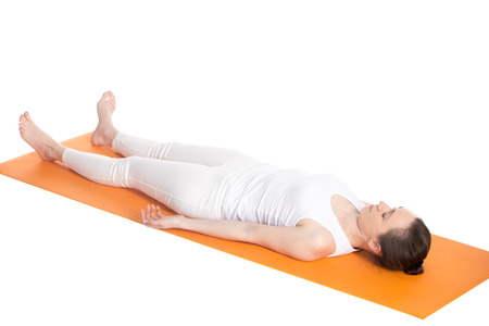 breathing: Sporty beautiful young woman in white sportswear lying with closed eyes on orange mat in Shavasana (Savasana, Corpse Pose), studio shot, isolated, full length three-quarters view