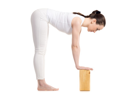 ardha: Sporty beautiful young woman in white sportswear doing variation of Standing Half Forward Bend, Ardha Uttanasana pose with wooden blocks, studio full length shot on white background, isolated