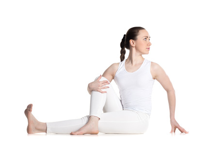 Sporty beautiful young woman in white sportswear sitting in Vakrasana, easy variation of Half lord of the fishes pose, Ardha Matsyendrasana, studio full length isolated shot, front view