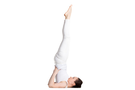 supported: Sporty beautiful young woman in white sportswear doing Supported Shoulderstand exercise, Salamba Sarvangasana, studio full length isolated shot, side view