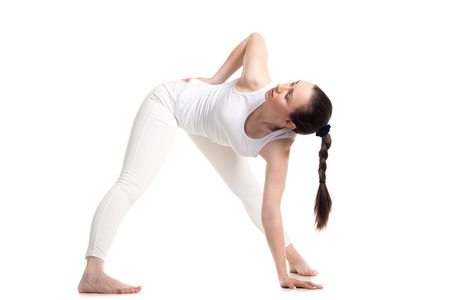 trikonasana: Sporty beautiful young woman in white sportswear standing in variation of Trikonasana yoga pose, studio full length three-quarters view on white background, isolated