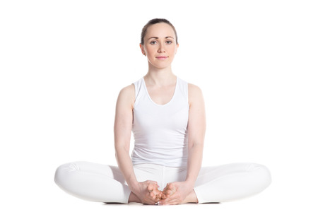 baddha: Sporty beautiful smiling young woman in white sportswear sitting in baddha konasana, bound angle, cobbler, butterfly pose, studio full length isolated shot, front view Stock Photo