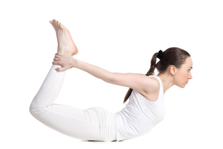 dhanurasana: Sporty beautiful young woman in white sportswear doing backbend exercises, lying in dhanurasana, Bow Pose, studio full length side view, isolated Stock Photo