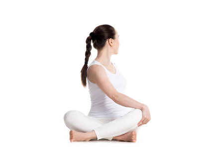 Sporty beautiful young woman in white sportswear practicing yoga, sitting cross legged in Revolved easy pose, spinal twist, parivrtta sukhasana, studio full length isolated shot, front view Stockfoto