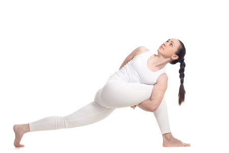 revolved: Sporty beautiful young woman in white sportswear doing lunge exercise for spine flexibility, standing in parivritta parshvakonasana variation with hands behind back, full length isolated studio shot Stock Photo
