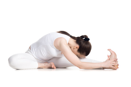 knee bend: Sporty beautiful young woman in white sportswear sitting in head to knee forward bend pose, doing Janu Sirsasana, studio full length isolated shot