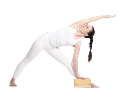 trikonasana: Sporty beautiful young beginning yoga female student standing in Utthita Trikonasana, Extended Triangle Pose leaning on yogic wood brick, studio full length profile view on white background, isolated