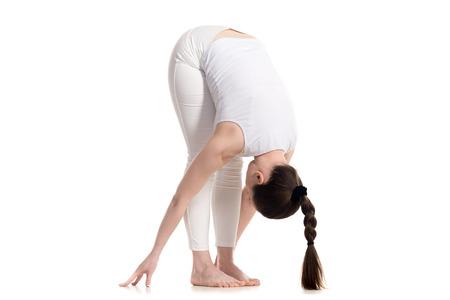 namaskar: Sporty beautiful young woman in white sportswear with cute long braid hairstyle doing Standing Forward Bend, Uttanasana pose, studio three-quarters view, isolated, part of Surya Namaskar series Stock Photo